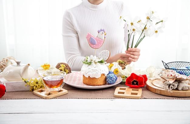Il processo di decorazione di una composizione con la torta pasquale. il concetto di arredamento per le vacanze di pasqua.