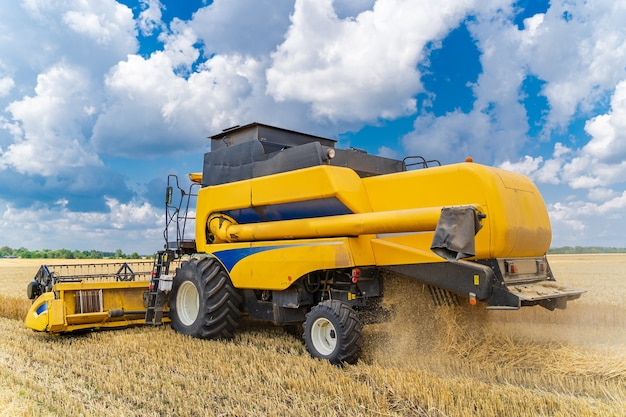 Process of gathering a ripe crop from the fields. combine harvester in action on wheat field. closeup