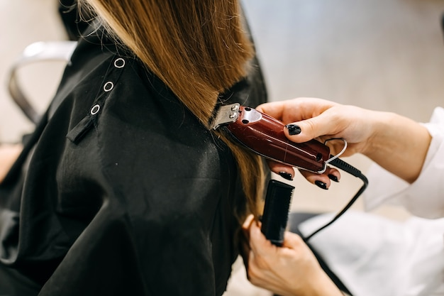Process of hair cutting at a beauty salon, using a hair clipper