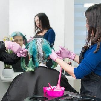 Обработать краску для волос в салоне красоты два парикмахера наносят краску на волосы во время обесцвечивания корней волос.