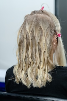 Process of hairstyling with curler for blond woman after hair bleaching.