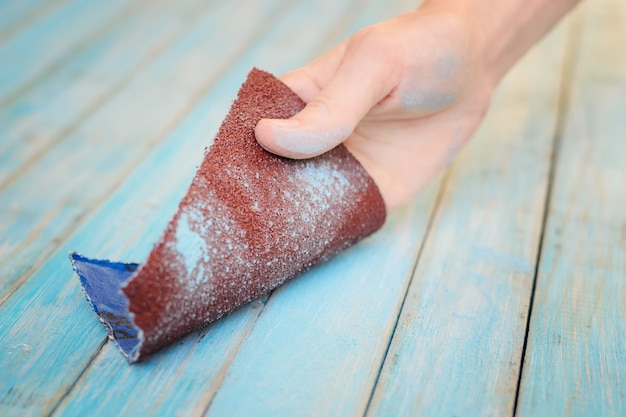 Process of hand polishing wooden board surface with a sandpaper