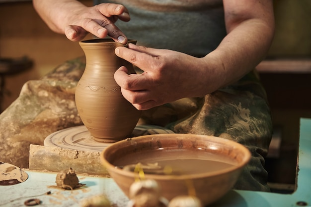 Process of making clay pot on a potter's wheel in workshop