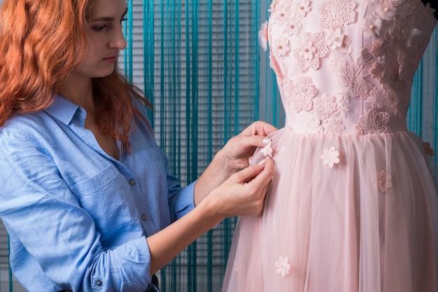The process of making clothes. professional designer, handmade craftsman, sews flowers on a pink dress, on a mannequin, in a workshop. tailoring, women's dress. pink wedding dress