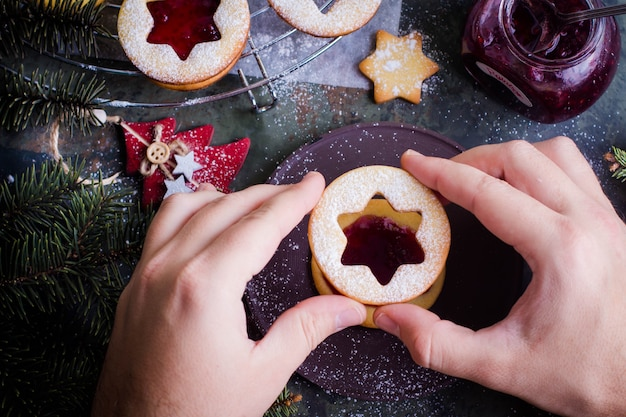 Process making of cookies by hand. christmas linzer cookies with raspberry jam