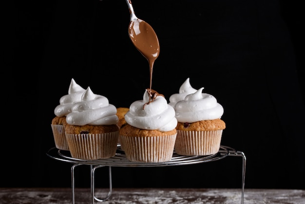 The process of making cupcakes, coating a cream from a pastry bag in the hands of a pastry chef.