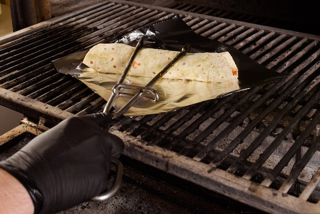 The process of making a foil grilled burrito. mexican dish.