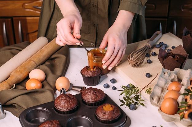 Process making homemade chocolate cupcake with cream