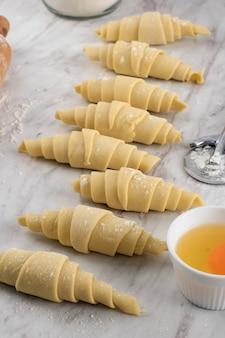 白い大理石のテーブルの上に、自家製クロワッサンを作るプロセス。キッチンでのベーキングプロセス