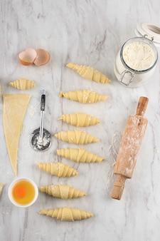 自家製クロワッサン、生クロワッサンの準備を自宅で焼くプロセス。白い大理石のテーブルの上にさまざまなサイズのクロワッサン