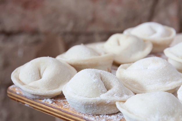 Process of making homemade pelmeni (dumplings) on wooden board.