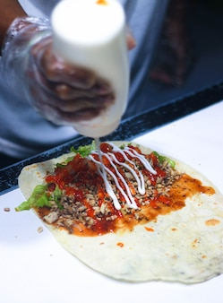 The process of making kebabs with chili sauce