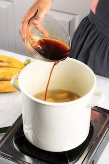 コラック(バナナとサツマイモのコンポート)の製造プロセス:液体パームシュガーを鍋に注ぎ、ラマダンの朝食のためにコレックを段階的に調理します。写真の女性の手