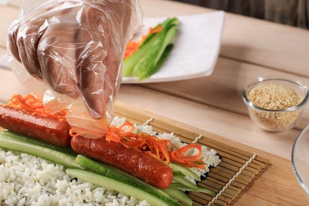 Процесс изготовления корейского ролла кимбап (кимбоб или кимбап), сделанный из вареного белого риса (бап) и различных других ингредиентов, завернутый в умывальник из морских водорослей. положите морковь на рис