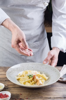 Process of making a pasta dish. chef sprinkles italian pasta with grated cheese.