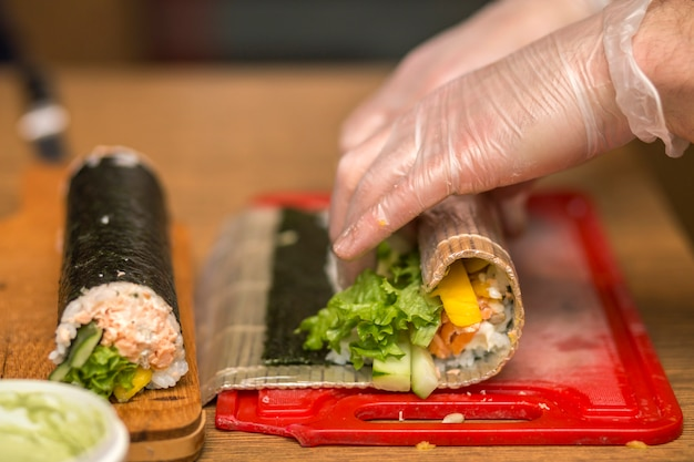 Process of making sushi and rolls. close-up of man chef hands preparing traditional japanese food at home or in restaurant on kitchen table.