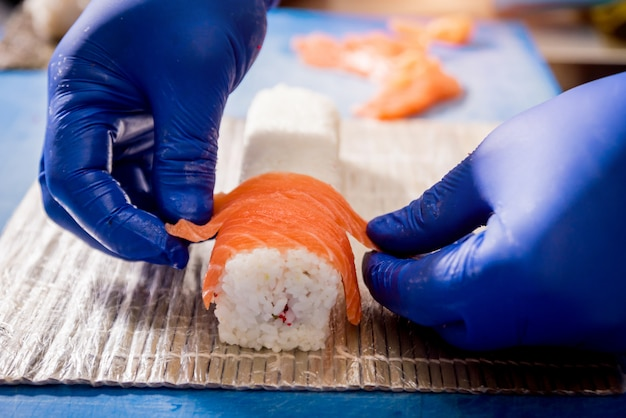 Process of making sushi and rolls at restaurant kitchen. chefs hands with knife