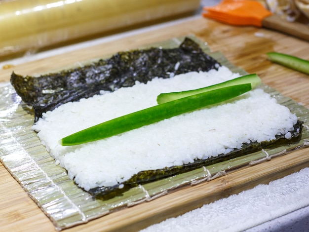 The process of making sushi and rolls with cucumber. rice on nori sheet