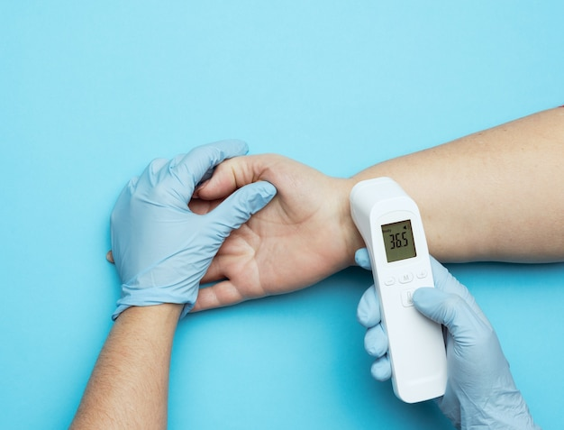 Process of measuring body temperature on the wrist with a non-contact thermometer, close up