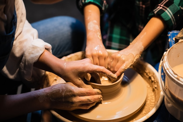 The process of modeling clay dishes on a potter's wheel, the hands of a young girl and a child.