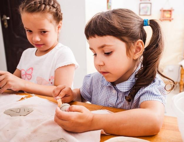 塑像用粘土からのプロセスモデリング図。子供たちはテーブルに座っています