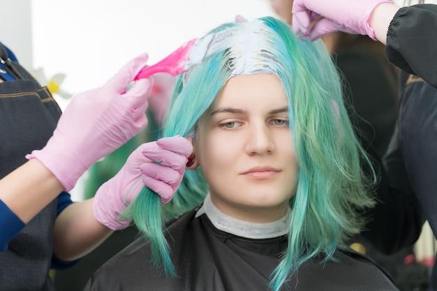 Процесс обесцвечивания корней волос в парикмахерской. два парикмахера в перчатках используют розовую кисть, нанося краску молодой взрослой клиентке с изумрудным цветом волос.