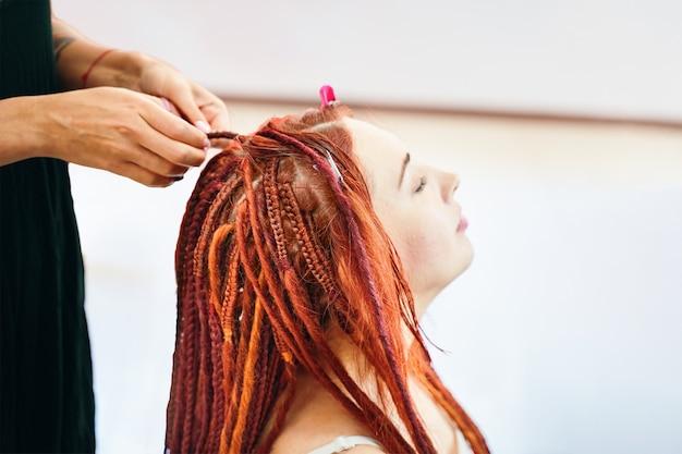 ビューティーサロンで頭に三つ編みを編むプロセスは、赤毛の女の子をクローズアップします。