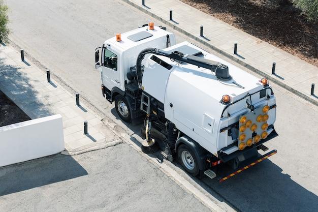 Процесс уборки улицы современной уборочной машиной. вид сверху.