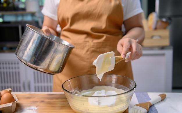 おいしい自家製ケーキとハロウィンカップケーキを調理するプロセス。自宅のキッチンで甘いもののデザートの材料を準備して混ぜる女性。