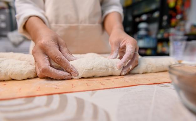 おいしい自家製ケーキを調理するプロセス。自宅で甘いデザートの材料を準備して混ぜる女性。