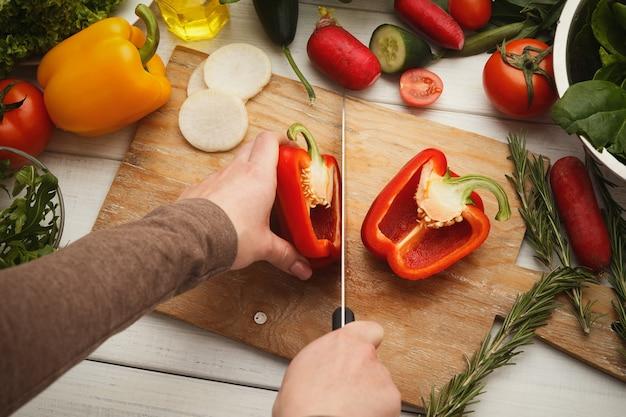 新鮮な野菜から作られた伝統的なスペインの冷たいスープ、ガスパチョを調理するプロセス。新鮮な赤唐辛子を切る女性の手、上面図