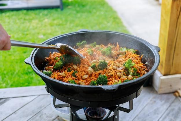 Процесс приготовления полезных овощей в казане на огне на улице