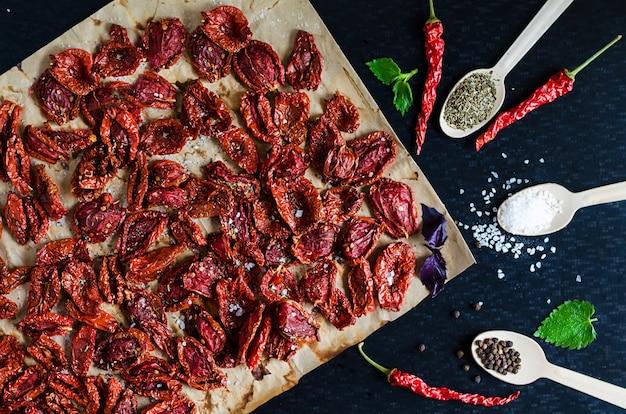Процесс приготовления домашних вяленых на солнце ломтиков красных помидоров со специями базилика и орегано. традиционная итальянская средиземноморская кухня. плоская планировка, вид сверху