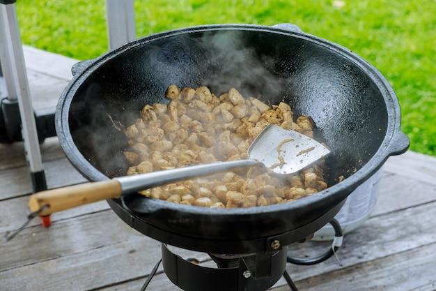 Процесс приготовления мяса для гуляша в казане на открытом воздухе.