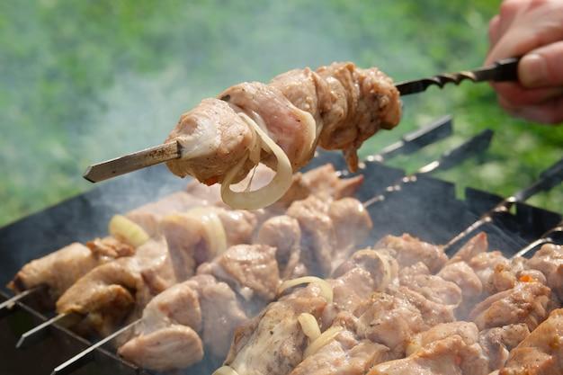 屋外で漬け肉からシャシリクを調理するプロセス