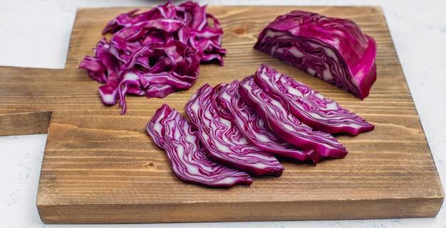 Процесс приготовления нарезки блюд из свежих витаминных салатов из красной капусты на разделочной доске, вид сверху