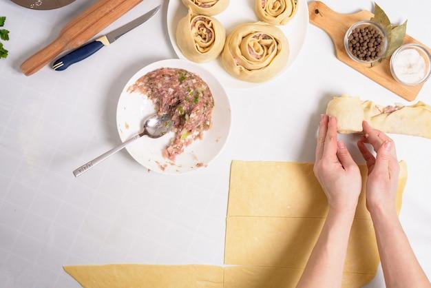 집에서 우즈벡 만티를 요리하는 과정에서 재료는 고기, 야채, 반죽입니다. 여자의 손은 manti를 조각합니다.