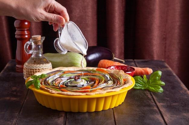 실리콘 베이킹 접시에 야채 나선형 타르트를 요리하는 과정 여자는 파이에 크림을 붓는다