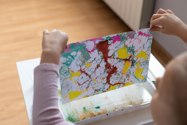 墨流しを作成するプロセス。子供は水に絵の具で描く