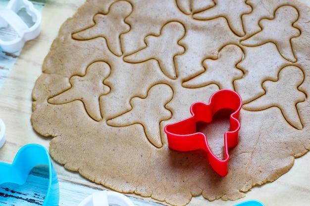 ジンジャーブレッドマンクッキーを扱うプロセスは、白い木製のテーブルにカラフルなクッキーカッターの周りの紙を焼くのに赤いジンジャーブレッドマン型切断ジンジャーブレッド生地を使用します。上面図