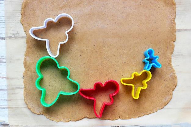 진저 브레드 남자 쿠키를 다루는 과정 흰색 나무 테이블에 다채로운 쿠키 커터 주위에 종이 굽기에 빨간 진저 브레드 남자 금형 절단 진저 반죽을 사용합니다. 평면도