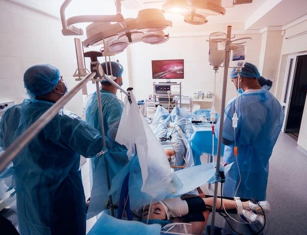Процесс операции гинекологической хирургии с использованием лапароскопического оборудования. группа хирургов в операционной с хирургическим оборудованием