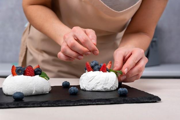 ベリーケーキを作るプロセス。女性の手がメレンゲを飾ります。アンナパブロバケーキ。