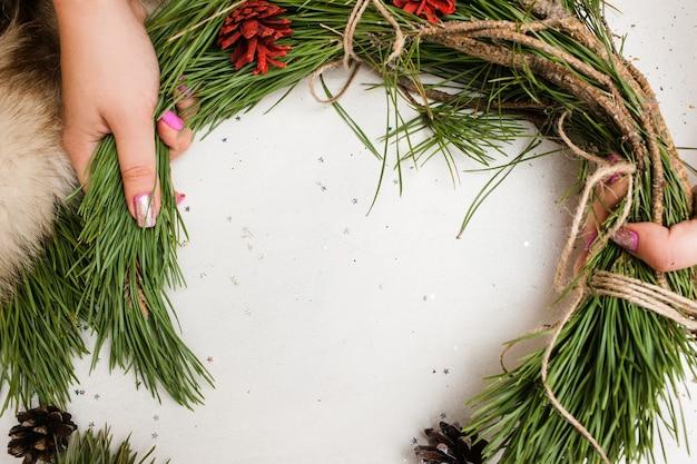 Процесс изготовления рождественского венка неузнаваемой женщиной
