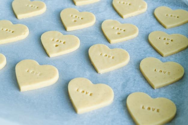 Процесс изготовления готового печенья в форме сердца со словом любовь. концепция кондитерских изделий.