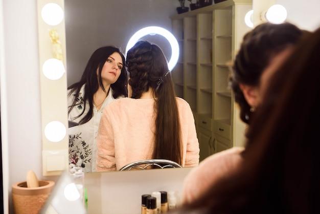 メイクのプロセス。モデルの顔にブラシを使用してメイクアップアーティスト。美容サロンのインテリアで若い女性の肖像画。