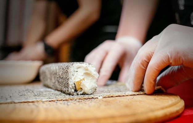 寿司を作るプロセス、木製の机の上にポピーと奇妙な巻き寿司