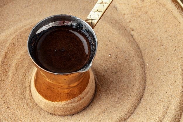 砂の上のcezveのトルコでのコーヒーの準備のプロセス
