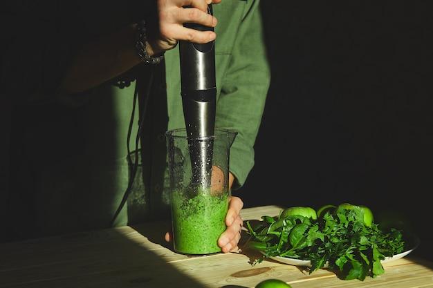 ミキサーで緑のデトックススムージーを準備するプロセス、若い男の手が自宅で新鮮な果物と緑のほうれん草の健康的なスムージーを調理、ライフスタイルのデトックスコンセプト、ビーガンドリンク。