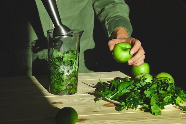 ミキサーで緑のデトックススムージーを準備するプロセス、若い男の手は、新鮮な果物とほうれん草の健康的なスムージーを調理します。ライフスタイルのデトックスコンセプト。ビーガンドリンク。
